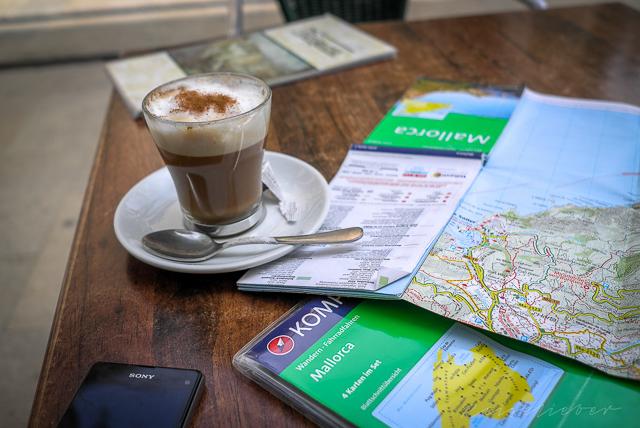 Capuccino und Landkarten auf einem Tisch in einem Café