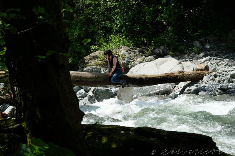 Frau benutzt Baumstamm als Brücke über Fluss